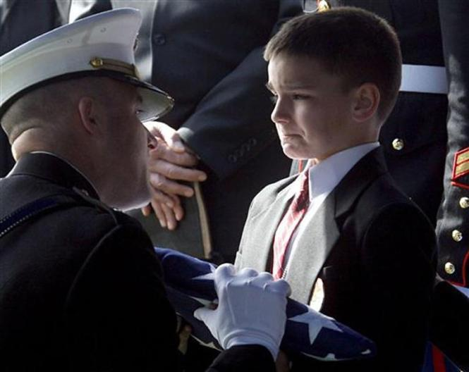 2. A little boy is given the U.S. flag at his soldier father's funeral.