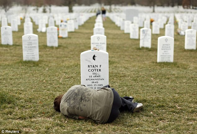 The sister of a fallen soldier collapses at his grave.