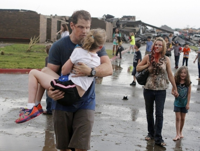 An injured family walks away from their destroyed neighborhood in Moore, Oklahoma.