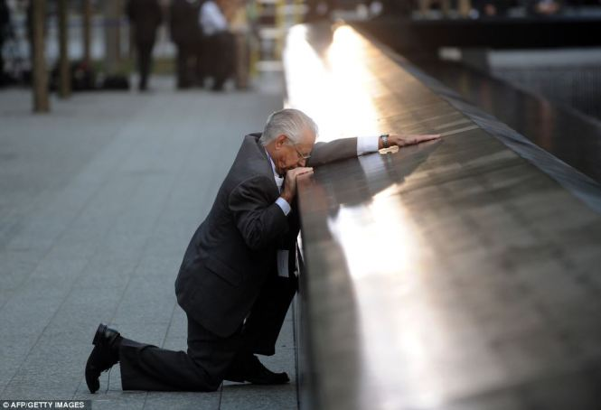 This man kneels at the 9/11 memorial over the loss of his son.